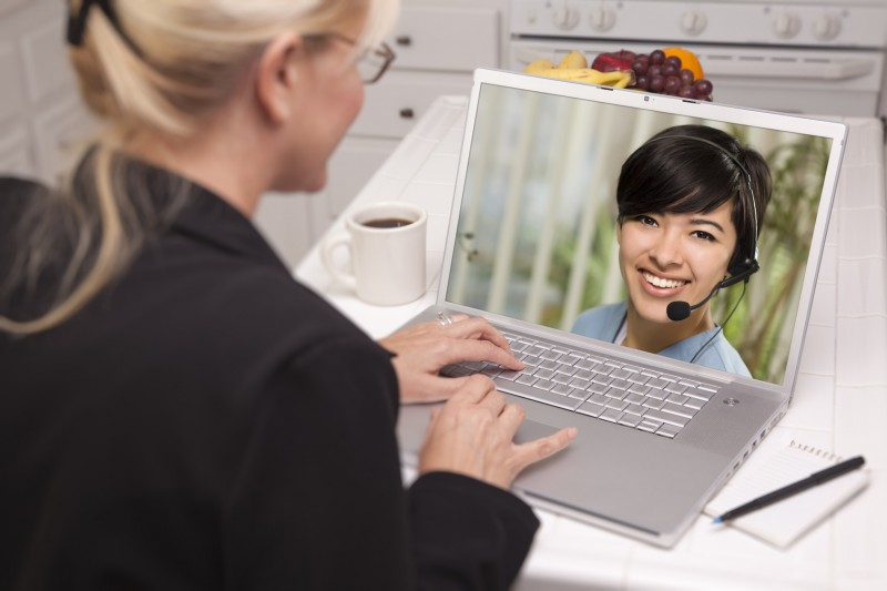 Over Shoulder of Woman In Kitchen Using Laptop - Online Chat with Nurse or Doctor on Screen.